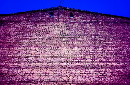 new addition: violet lilian pink brick wall with two small square dark windows under triangle roof against blue summer sky. brick wall under corrugated metal roof. unban brick background