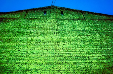 grass emerald green bright brick wall with two small square dark windows under triangle roof against blue summer sky. brick wall under corrugated metal roof. unban brick background