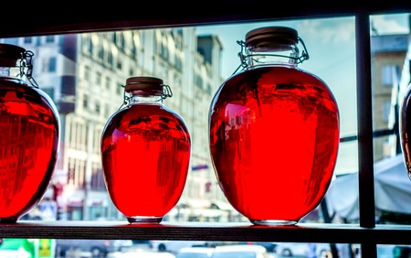 wärmflasche: round bottles with bloody red transparent liquid stand on wooden shalved against big window with street in small family restaurant, fruit compote bottled and placed as a decoration Lizenzfreie Bilder