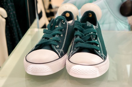 plimsoll: top view to green sneaker shoes wait for its master in sale season in big fashion shop. dark blue sport shoes with round white security magnet tag stay on white high shelf against modern clothes