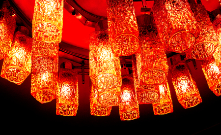 side view to part of fire red orange bronze round decorative modern shaped lamps on ceiling against dark background, many modern ceiling lamps with abstract ornament