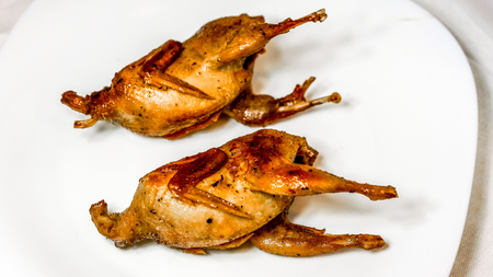 quail: top view to two quail with crispy crust on big white plate. PRoasted Partridge, quail grilling on sunny day. Culinary concept with delicious food.