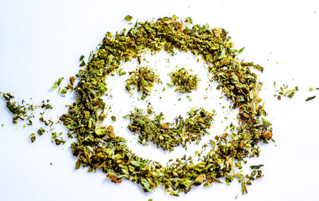 smiled: make me smile with cannabis green grass. smiled smile made by dry cut green cannabis before using. Marijuana Bud Cannabis Close Up On white background