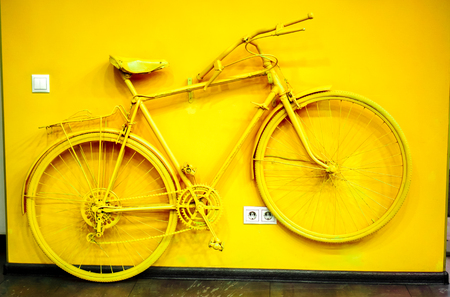 wall socket: golden yellow bicycle as decoration and power socket and switch on the wall. old painted bicycle attached to the wall in art office toned to golden color. vintage bicycle on decorative color wall