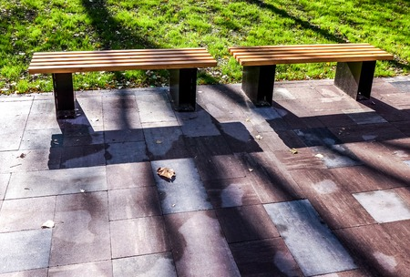 long mystery shadows on two strong wooden bench with metal legs stay on grey pawing stones near green meadow with colorful trees in sunny park. beautiful sunny landscape