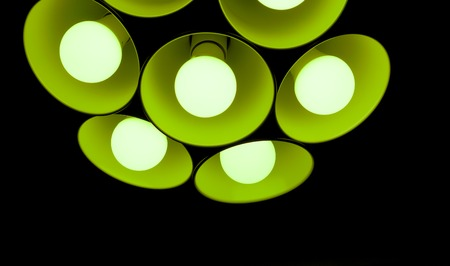 modern green emerald chandelier with seven round plafonds with lamps inside them against black background. electric fixture with round plafonds from glass