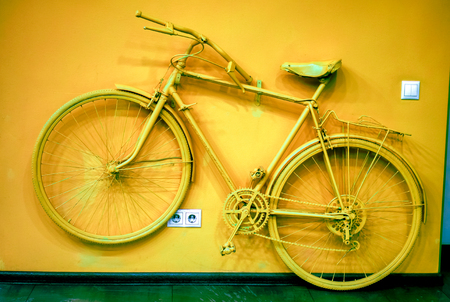 wall socket: old man bicycle toned to bronze color and connect to wall as decoration near white power socket and switch. old painted bicycle in art office tone to orange bronze color. vintage bicycle on color wall
