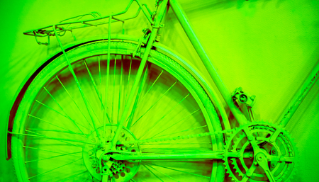 juicy green emerald wheel, crankset and part of frame as part of old painted bicycle used for decoration in office. vintage bicycle on decorative color wall in art office Stock Photo