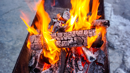 big bright spurts of flame illuminate the twilight and warm everything near. Wood burning in the brazier. Flames fire. Preparation for cooking barbecue. fire flame texture as natural background