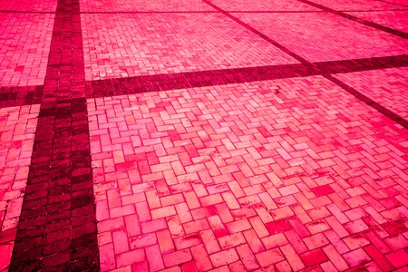strong burgundy bloody diagonal layed pavement tiles with black horizontal and vertical lines, paving stone with light and dark color as texture