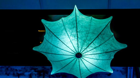 blue chandelier with light inside as umbrella against black background. umbrella lamp hangs his cane up as decoration of modern night club. Lighting umbrella shape from small lamps at night