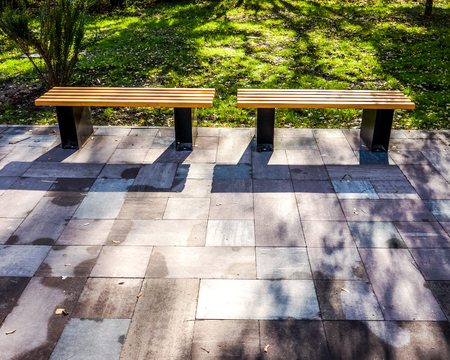 spring summer sun made shadows on two strong wooden bench with metal legs stay on grey pawing stones near green meadow with colorful trees in sunny park. beautiful sunny landscape Stock Photo