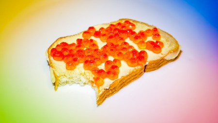 spawn: rainbow light on delicious appetizing bred peace with fish caviar without small peace cut by teath. fresh fish yellow golden caviar on peace of white bread. Sandwich with caviar as holiday food