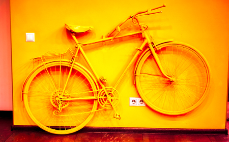 wall socket: art vintage bicycle toned to acid orange color and connect to wall as decoration near power socket and switch. old painted bicycle in art office tone to orange color. vintage bicycle on color wall