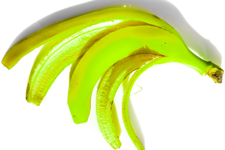 isolate green bright banana skin without ripe inside lay on white plate as human five fingers. banana skin isolated on white background in sunshine