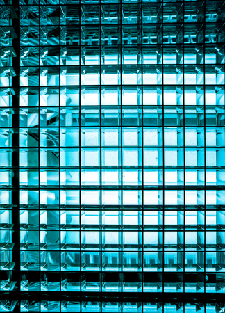 side part of turquoise blue color metal mesh with a square pattern on a bright lamp with gradient effect , close-up of movie illuminant against black background
