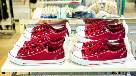 top side view to pairs of new burgundy sneakers with white round security magnet tags stay on white shelf above clothes rack against colorful new clothes in big shop. lots of sneaker shoes on sale