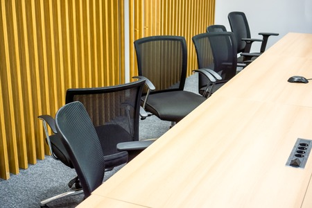 big wooden table with many black office armchairs chaoticly stands one by one against yellow wall with vertical lines. Classic meeting room with black armchairs with grid back after meeting