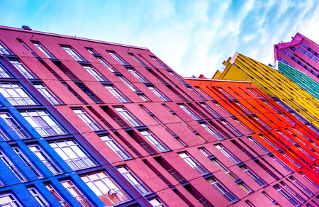 high blue burgundy yellow violet multi-storey houses stay one by one as place for people family live against blue sky with white clouds. Colourful multi-storey residential building above blue sky