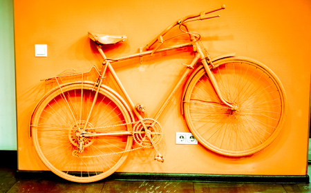 wall socket: vintage bicycle toned to acid orange color and connect to wall as decoration near power socket and switch. old painted bicycle in art office tone to orange color. vintage bicycle on color wall Stock Photo