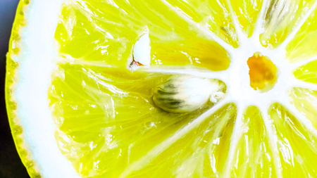 part of lemon slice. natural yellow green organic sweet juicy lime slice with white circle in the center, diagonal white lines to the skin and few small ivory seeds inside it. texture of fresh citrus lobule.
