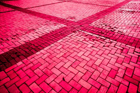 cross made with strong burgundy bloody diagonal layed pavement tiles with black horizontal and vertical lines, paving stone with light and dark color as texture Stock Photo