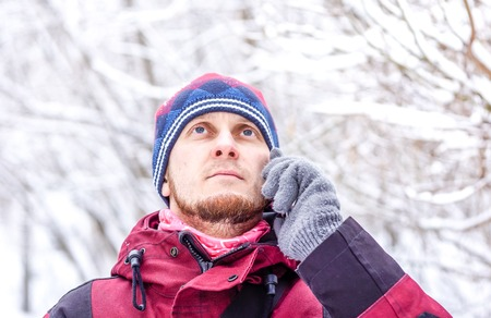 white man with brown beard in dark red clothes, heat with pompon and grey gloves speak on his smartphone against winter forest with snow on brunches. Portrait of young man with mobile phone
