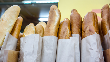 baguet: long and short sweet white french Baguettes in a paper bags stay as vertical lines on shop shelf and wait for its morning byers. Fresh baked rustic bread loaves in paper bags on market shelf