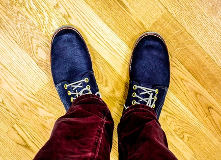shoelace: demi autumn deep blue big laither boots with golden circles and shoelace against wooden floor. Chukka boots and burgundy jeans against floor. Close up view on mans legs