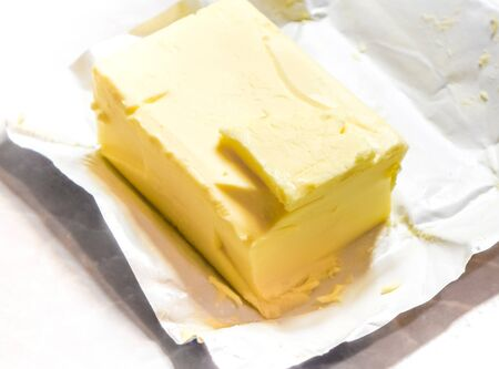 butterfat: slice of butter on big butter brick with cracked made by foil package. Ivory block of butter laying on foil wrapping with cracks made by knife. Creamy butter in its unwrapped foil paper