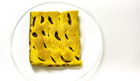 yellow not finished homemade cake made of raw dough with plumps and texture-baked dough cut into square against plate. Peace of home holiday cake as best addition to a cup of coffee or tea