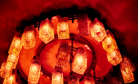 bright coral red orange decorative modern shaped lamps on ceiling against dark background, many modern ceiling lamps with abstract ornament as luxury chandelier