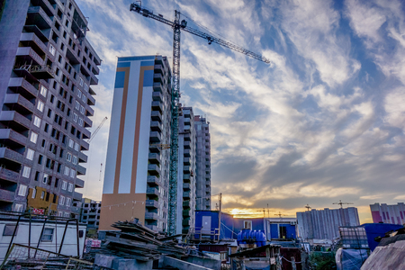 storey: ivory multi-store housing complex with autumn golden yellow grass in sunset sky with white clouds. Building cranes in front of a multi-storey building under construction which stay one by one