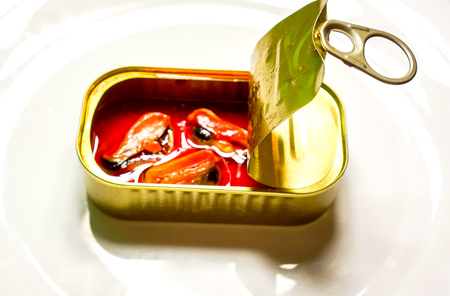 small square brilliant can with three orange mussels that swimming in orange golden oil against white background. Food Still Life with seafood delicacies. marinated in oil mussels in a can Stock Photo