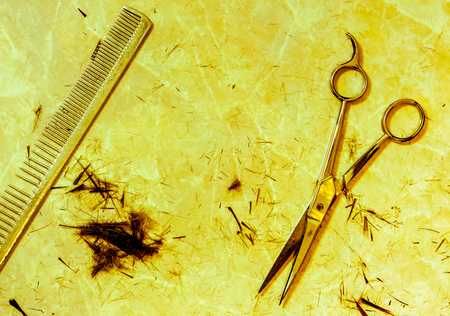 yellow light on open silver hair cutting shears and vintage metal steel comb against small spots of dark cutting hair and many small filaments on the table after haircut. Work still life of hairdresser Stock Photo