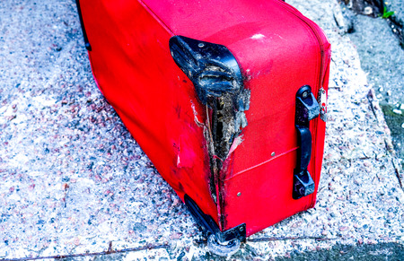 red broken traveling luggage with black wheels lay on grey ground. Juicy red traveling suitbag without one wheel Stock Photo
