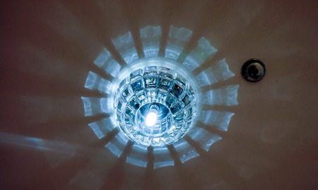 reflection in mirror: mystery circles shine around big lamp with light. Circle big chandelier with crystals, round mirror and lamps which made reflection on ceiling as star light. luxury chandelier with briliants and light