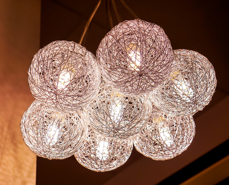 big ball: clean crystal white modern art luxury chandelier made with balls with lamp inside every one, which connet to beautiful big flower. Lighting ball hanging from the ceiling on the black background