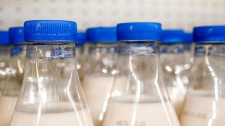 ショップで金属の背景に牛乳中のペットボトルに小さな垂直線でラウンド、青いカバーの軍隊、朝食を準備するための酪農製品としての牛乳瓶を待 写真素材