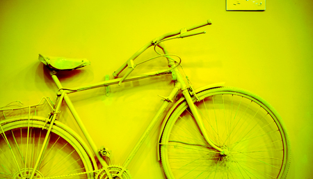close up of bicycle as decoration on the wall. old painted bicycle attached to the wall in art office toned toacid green yellow color. vintage bicycle on decorative color wall Stock Photo