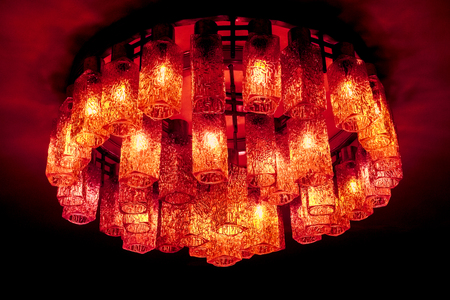 orange red crimson decorative modern shaped lamps on ceiling against dark background, many modern ceiling lamps with abstract ornament as luxury chandelier