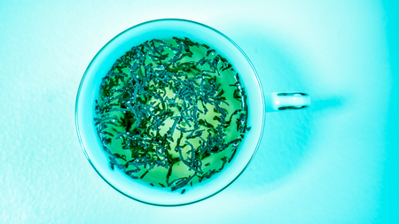 Turquoise Freshly Brewed Tea With Tea Leaves Floating On Top In A White Cup With  A