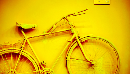 vintage furniture: close up of bicycle as decoration on the wall. old painted bicycle attached to the wall in art office toned to yellow golden color. vintage bicycle on decorative color wall