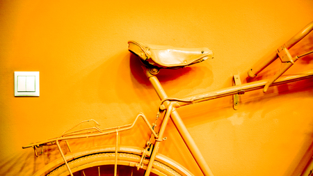 wall socket: white socket near bright bronze coral part of wheel, part of frame and saddle as part of old painted bicycle used for decoration in office. vintage bicycle on decorative color wall in art office Stock Photo