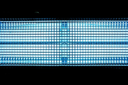 spotlight: Blue metal mesh with a square pattern on a bright lamp with gradient effect on a black background as horizontal line, close-up of movie illuminant, model the motion of electrons,