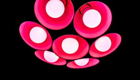 peace of big flower modern red coral chandelier with seven round plafonds with lamps inside them against black background. electric fixture with round plafonds from glass Stock Photo