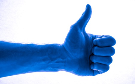 Like concept. Voting hand on blue background. One hand making thumb up gesture. toned to deep blue mans hand Stock Photo