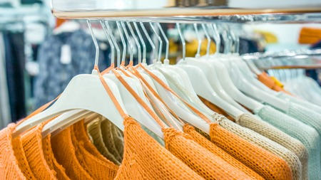 store shelf: front view to orange raglans with a large pattern knit on white shopping similar racks on clothes shop. bright different clothes on the rack before sale season. new collection in clothes luxury shop