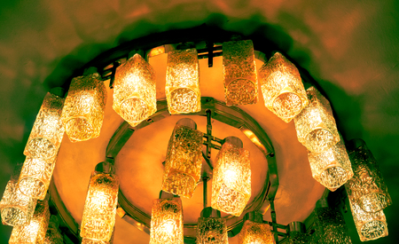 many fire yellow orange decorative modern shaped lamps on ceiling against dark background, many modern ceiling lamps with abstract ornament as luxury chandelier Stock Photo
