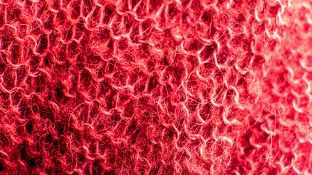 burgundy red warm wool knitted texture with aerial loops and clearly discernible pattern of knitting. colorful knitted fabric background close up. Warm wool scarf sweater clothes